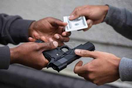 Close-up Of Two Hands Exchanging Black Handgun For Banknote