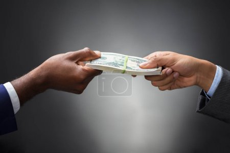 Close-up Of Two Business People's Hand Holding Bundle Of Banknotes Against Gray Background