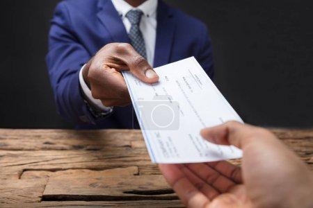 Photo pour Gros plan de la main d'un homme d'affaires qui remet un chèque à un collègue sur un bureau en bois - image libre de droit