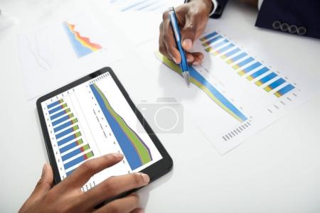 Close-up Of Two Businesspeople Using Digital Tablet While Working On Graph On Desk At Workplace