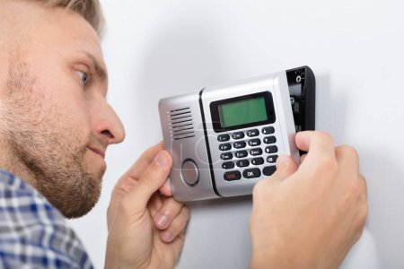 Close-up Of Repairman Installing Security System Against Wall