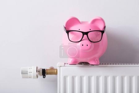 Photo pour Gros plan de Thermostat et tirelire avec lunettes sur radiateur contre mur blanc - image libre de droit