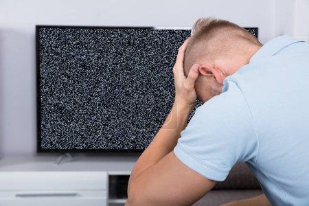 Photo pour Frustré homme assis sur un canapé devant la télévision avec aucun Signal - image libre de droit