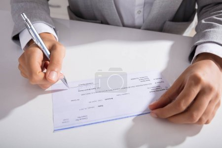 Close-up Of Person Hand Signing Cheque With Pen At Desk