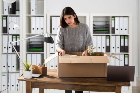 Sad Young Businesswoman Packing Her Belongings In Cardboard Box At Workplace