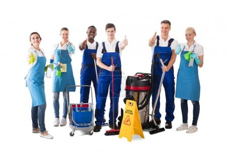 Group Of Happy Janitors Gesturing Thumbs Up On White Background