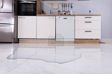 Photo pour Gros plan de l'eau déversée sur le plancher de la cuisine à la maison - image libre de droit