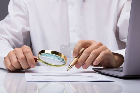 Midsection Of Businessman Examining Invoice With Magnifying Glass At Desk