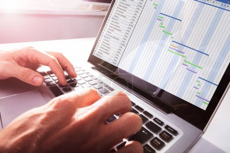 Close-up Of Businessman's Hands Working On Gantt Chart On Laptop At Office