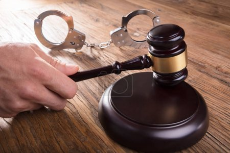Close-up Of A Judge Hand Striking Gavel With Handcuffs On Wooden Desk In Courtroom