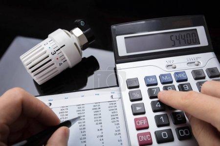 Photo pour Gros plan d'une main humaine calculant un rapport financier à proximité d'un radiateur thermostatique - image libre de droit