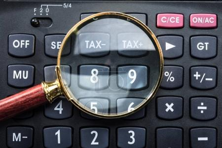Close-up Of Magnifying Glass On Black Calculator