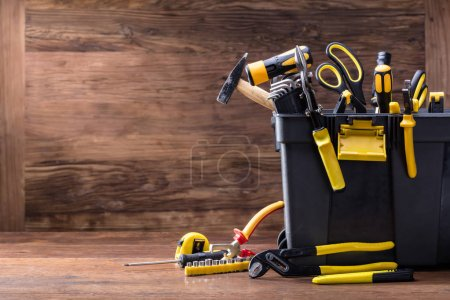 Photo for Plastic Black Container With Many Tools On Wooden Desk - Royalty Free Image