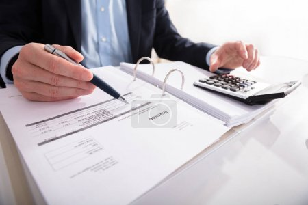 Close-up Of A Businessperson's Hand Checking Invoice With Calculator At Workplace