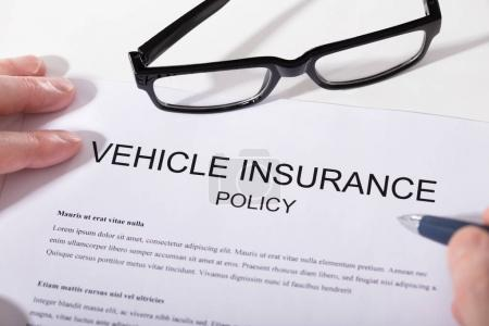 Elevated View Of Person's Hand Holding Pen Over Vehicle Insurance Policy Form