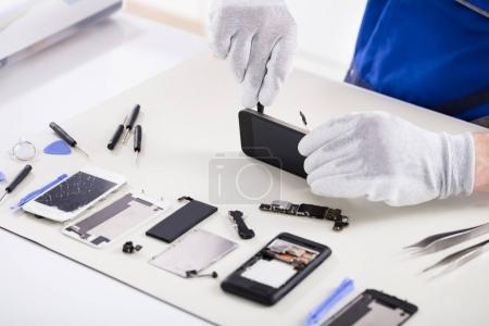 Photo for Close-up Of A Human Hand Repairing Smartphone With Screwdriver - Royalty Free Image