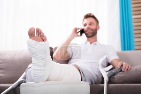 Foto de Joven feliz con pierna rota sentado en el sofá hablando en Smartphone - Imagen libre de derechos