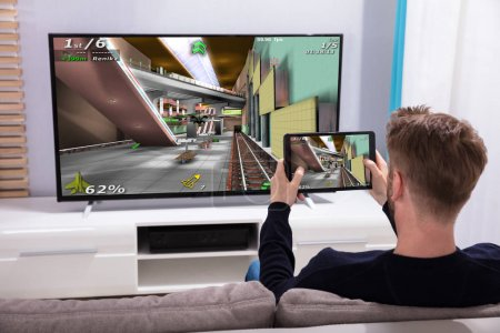 Photo for Rear View Of A Young Man Connecting Game On Television Through Wi-fi On Digital Tablet - Royalty Free Image