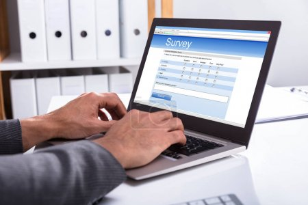 Close-up Of A Businessperson's Hand Filling Online Survey Form On Laptop In Office
