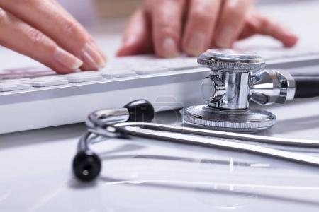 Close-up Of Woman's Hand Typing With Stethoscope On Desk