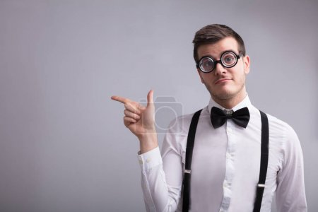 Young Man Wearing Spectacles Pointing On Grey Background