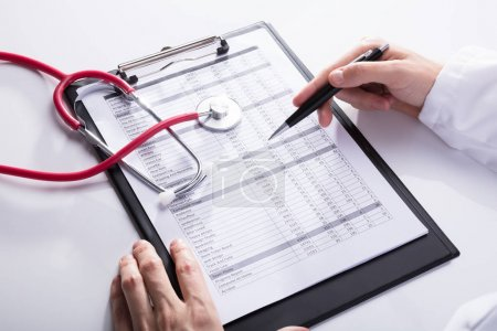 Photo for Close-up Of A Stethoscope Near Doctor's Hand Analyzing Report On Clipboard - Royalty Free Image