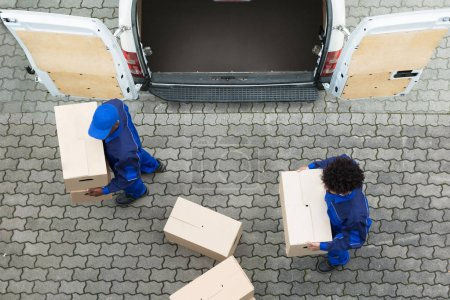 Photo for High Angle View Of Delivery Men Unloading The Cardboard Boxes From Truck - Royalty Free Image