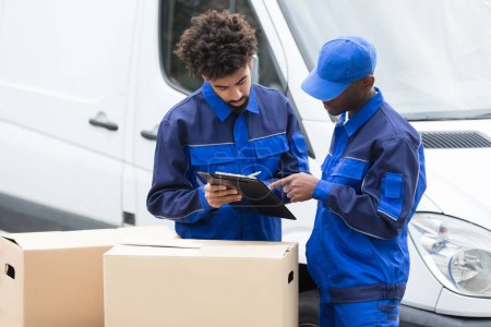 Delivery Man Writing On The Clipboard Over The Cardboard Boxes Standing By The Truck