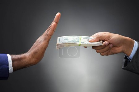 Close-up Of A Man's Hand Refusing Bribe Against Gray Background