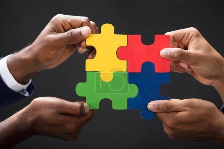 Close-up Of Business Partners Combining Puzzle Pieces On Black Background
