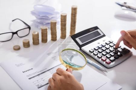 Businessperson's Hand Analyzing Bills With Magnifying Glass In Front Of Stacked Of Coins Graph