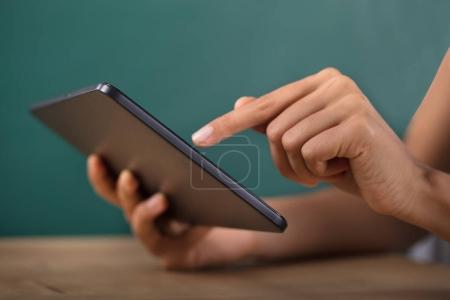 Primer plano de la mano de un maestro con tableta Digital