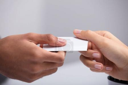 Photo for Close-up Of Two Businesspeople Hand Holding Blank White Card - Royalty Free Image