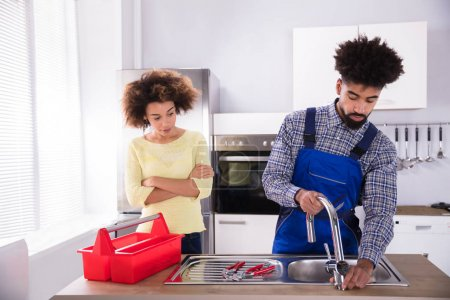Happy Woman Looking At Male Plumber Fixing Faucet In Kitchen