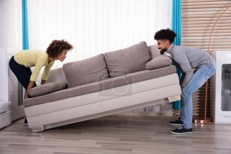 Photo pour Vue de côté de Young Smiling Couple levage canapé dans le salon - image libre de droit