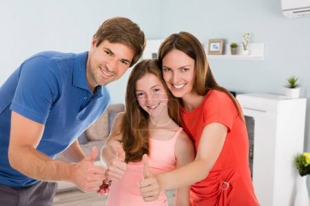 Portrait Of Happy Couple With Their Daughter At Home