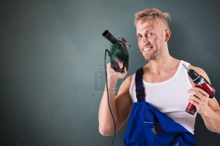 Portrait Of A Male Technician Holding Electric Drill And Screwdriver On Grey Background