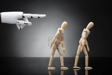 Close-up Of A Robot's Hand Giving Direction To Two Wooden Dummies On Grey Background
