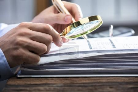 Close-up Of A Businessperson's Hand Looking At Invoice Through Magnifying Glass