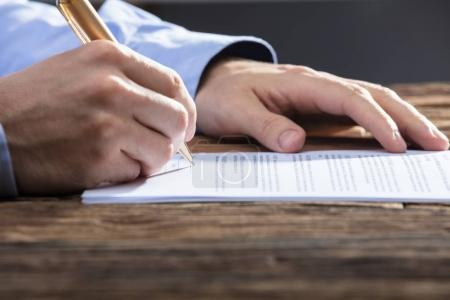 Photo for Close-up Of A Businessperson's Hand Signing Document On Wooden Desk - Royalty Free Image