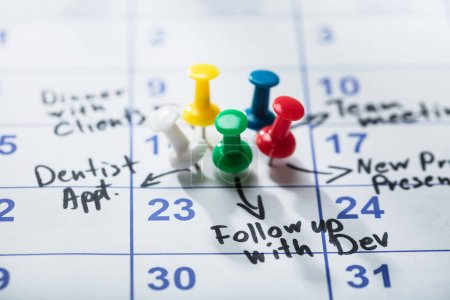 Colorful Pushpins Stuck On Calendar With Important Appointment Written On It