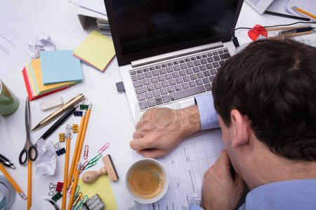 Close-up Of Exhausted Businessman Leaning His Head On Laptop Over The Messy Desk At Workplace