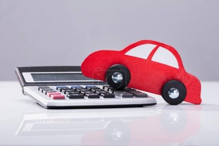 Close-up Of Red Car And Calculator Against Grey Background
