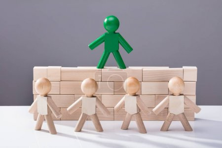 Row Of Figures In Front Of Figure Standing On Top Of Wooden Blocks
