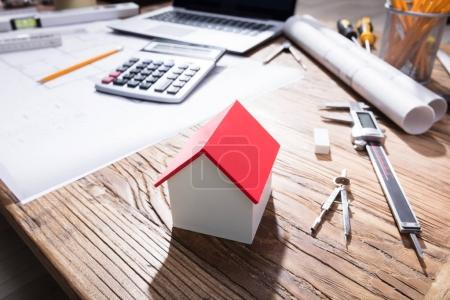 Close-up Of A House Model With Red Roof On Wooden Desk