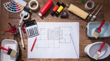 Elevated View Of Blueprint With Paint Brush And Tubes Of Paint On Wooden Background