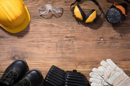 Close-up Of Yellow Hard Hat With Safety Equipment On Wooden Background