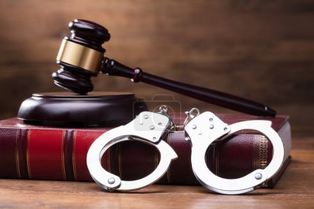 Photo for Gavel And Handcuffs On The Law Book Over The Wooden Table Background - Royalty Free Image