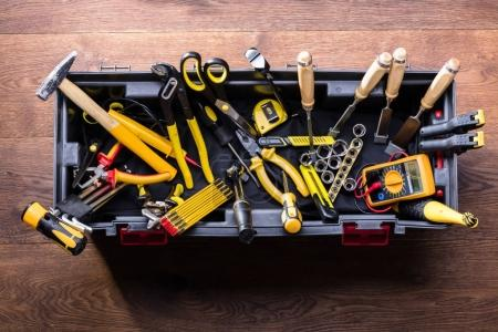 Elevated View Of Plastic Black Container With Many Tools On Wooden Table