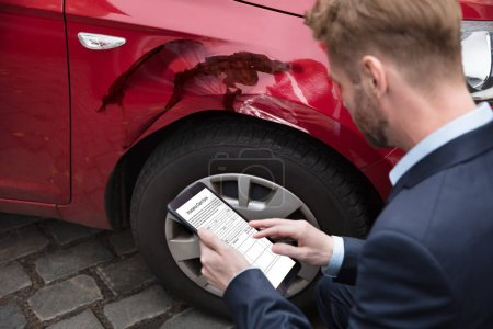Man Looking At Digital Tablet Screen Showing Insurance Claim Form Near Car